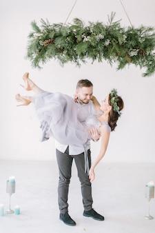 Groomsman en bruidsmeisje gekleed in grijze jurk dansen in witte kamer met bruiloft decoraties