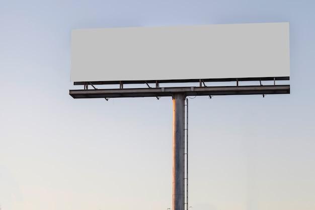 Groot aanplakbord reclamevertoning tegen blauwe duidelijke hemel