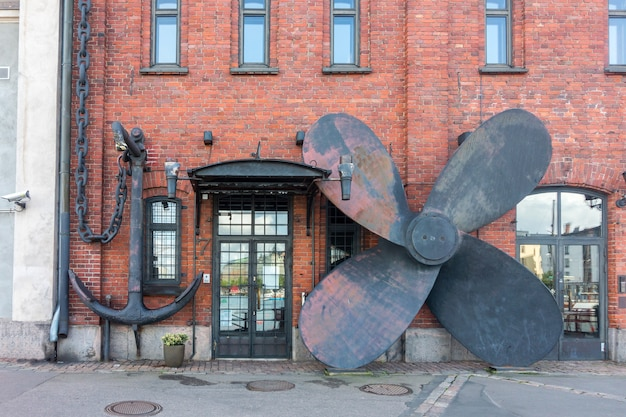 Groot anker en schroef van een oud schip op de muur van een oud huis, helsinki, finland