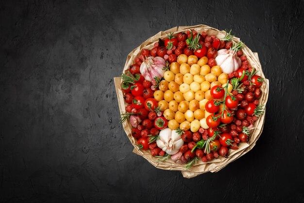 Groot boeket gemaakt van gerookte kaas, worstjes, tomaat, peper en knoflook verpakt in knutselpapier