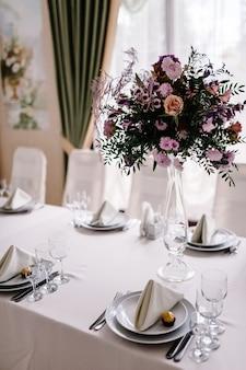 Groot boeket van verse roze, blauwe, witte bloemen en groen in vaas. bruiloft bloemen, bruids boeket close-up. decor op tafel, vintage stijl. decoratie objecten.