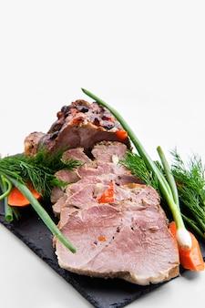 Groot brood van gebakken vlees dat met verse groenten wordt verfraaid die op wit worden geïsoleerd