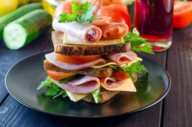Groot broodje met worst en kaas, komkommer en tomaat
