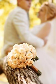 Groot bruidsboeket rozen tegen de achtergrond van de bruid en bruidegom in het bos