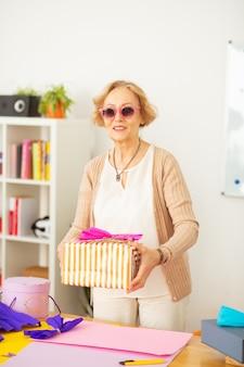 Groot cadeau. vrolijke oude vrouw die lacht terwijl ze een geschenkdoos vasthoudt