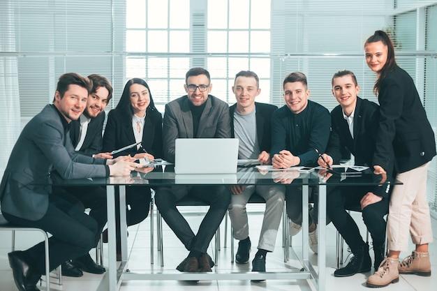 Groot commercieel team dat bij een bureau zit