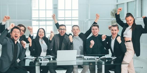 Groot commercieel team dat hun succes toont terwijl zij aan hun bureau zitten. het concept van teamwerk