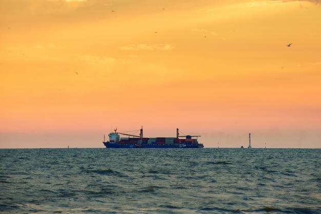Groot containerschip op zee met zonsonderganghemel