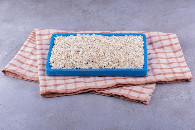 Groot dienblad met haver erop gestapeld, op een handdoek op marmeren achtergrond. hoge kwaliteit foto