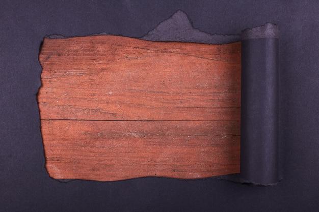 Groot gat in het zwarte papier. gescheurd. houten achtergrond. abstracte achtergrond.