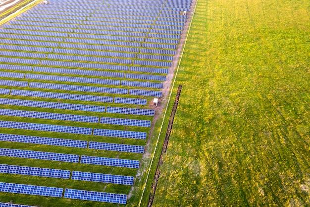 Groot gebied van fotovoltaïsch zonnepaneelensysteem dat hernieuwbare schone energie op groen gras produceert.