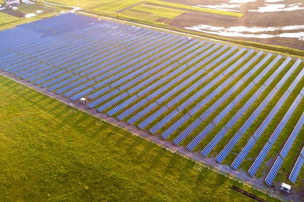 Groot gebied van het systeem van fotovoltaïsche zonnepanelen dat hernieuwbare schone energie op groene grasachtergrond produceert.