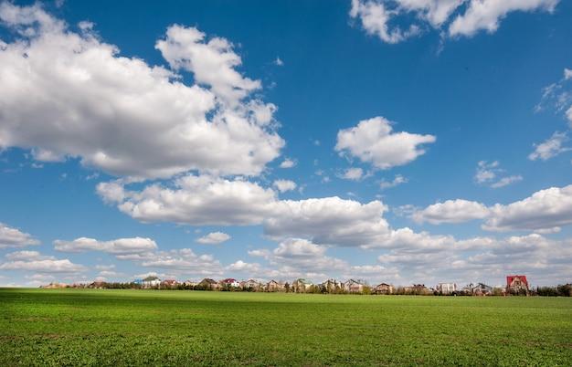 Groot gebied van wintertarwe, dorp en luchtwolken