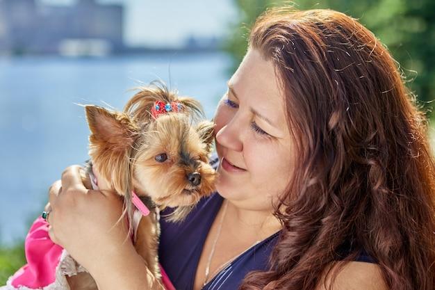 Groot gebouwde blanke vrouw houdt yorkshire terrier hond in haar armen
