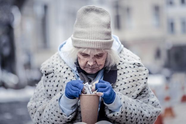 Groot geld. aardige dakloze vrouw die een biljet van honderd dollar neemt terwijl ze op straat zit
