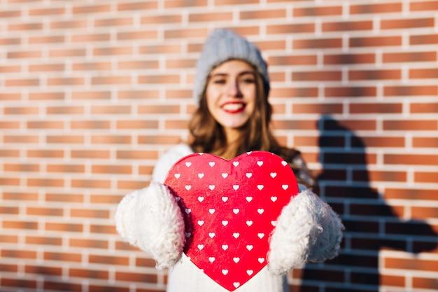 Groot gelezen hart, met meisje in warme witte handschoenen op muur buiten. ze heeft lang haar, glimlachend.