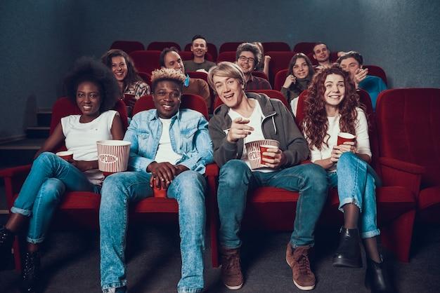 Groot gezelschap van vrienden kijkt komedie in de bioscoop.