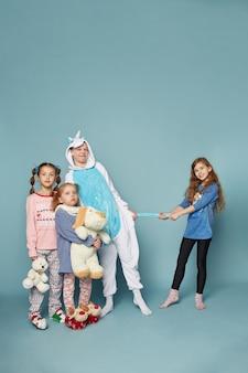 Groot gezin, kinderen hebben plezier en spelen 's ochtends op een blauwe. jongens en meisjes in nachtpyjama's, een vriendelijk groot gezin samen. ,