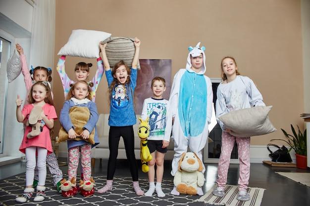 Groot gezin, kinderen hebben plezier en spelen 's ochtends thuis. jongens en meisjes in nachtpyjama's