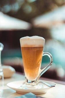 Groot glas laatste koffie op een tafel in onze deur naast het zwembad