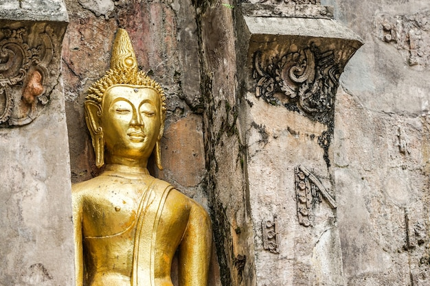 Groot gouden boeddhabeeld met oude muur als achtergrond.