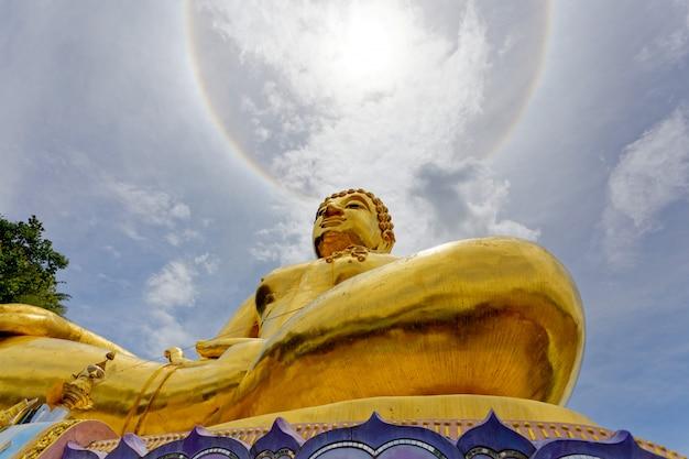 Groot gouden standbeeld boedha onder het licht van de coronarichtingzon.