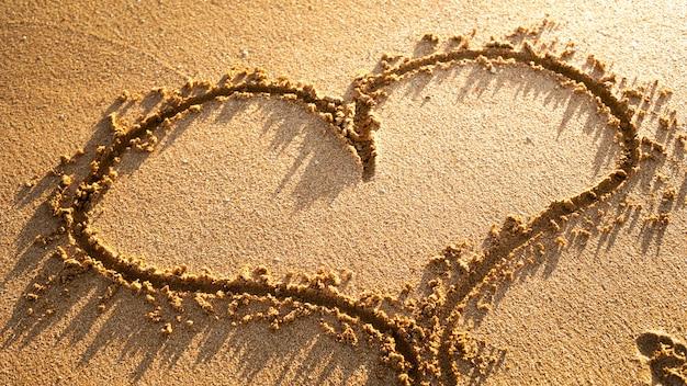 Groot hart met reliëf geschilderd op het zand van het strand.