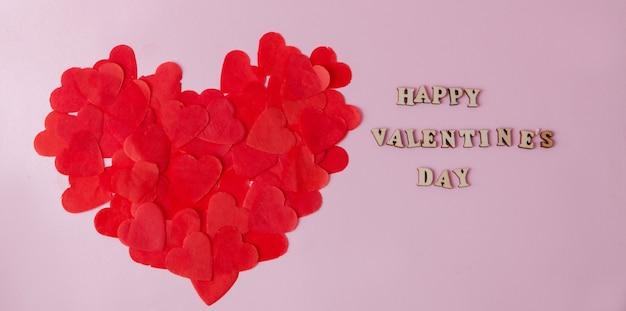 Groot hart van kleine papieren hartjes op een roze achtergrond met een inscriptie happy valentine's day.