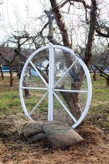 Groot houten wiel met zakken en hooibomen in de tuin