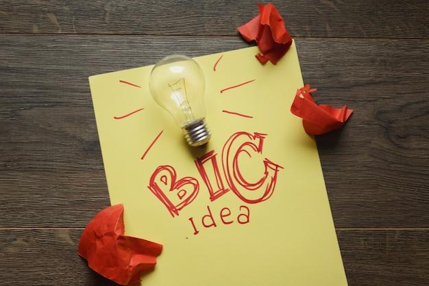 Groot idee met gloeilamp en rode verfrommelde papieren