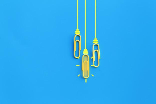 Groot ideeënconcept met paperclip, het denken, creativiteit, gloeilamp op blauwe achtergrond, nieuw ideeënconcept.