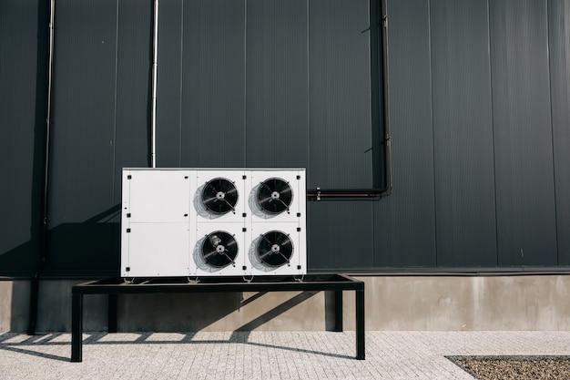 Groot industrieel ventilatorsysteem van de airconditioning buiten op een grijze muurachtergrond