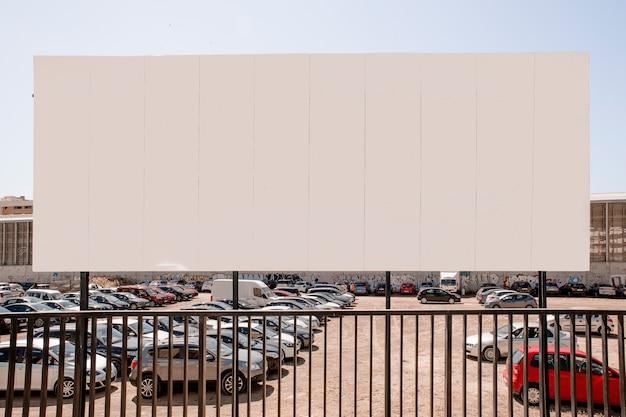 Groot leeg aanplakbord dichtbij de parkeerplaats