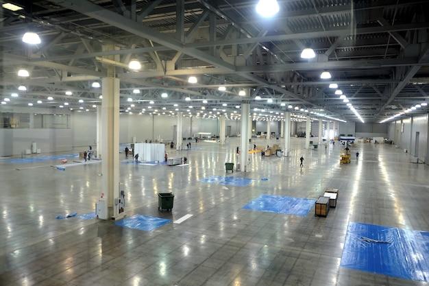 Groot leeg magazijn interieur in een industrieel gebouw met hoge verticale kolommen met en hoog plafond en kunstmatige verlichting horizontale weergave