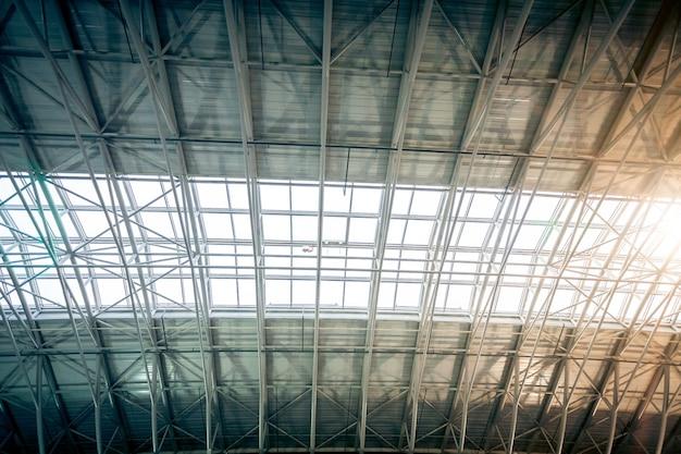 Groot metalen dak bij stedelijke terminal met zon die door ramen schijnt shining