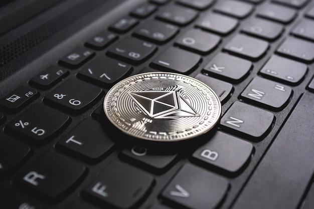 Groot muntstuk dat bovenop een zwart computertoetsenbord wordt geplaatst
