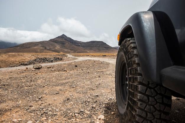 Groot off-road wiel van zwarte hoge sterke auto verkent de woestijn en de bergen op het platteland. alternatieve manier van reizen en levensstijl voor reizigers in reislust
