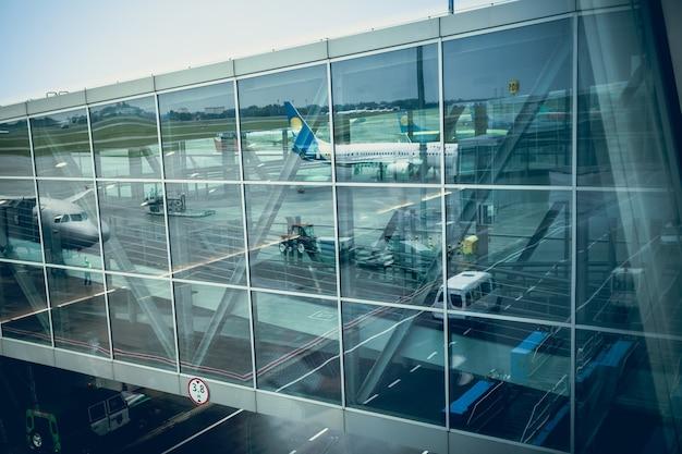 Groot passagiersvliegtuig dat in glasmuur van moderne luchthaventerminal nadenkt