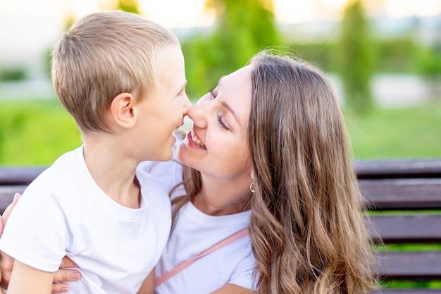 Groot portret van een moeder met haar zoontje in het park op een bankje in de zomer met plezier knuffelen, lachen en spelen