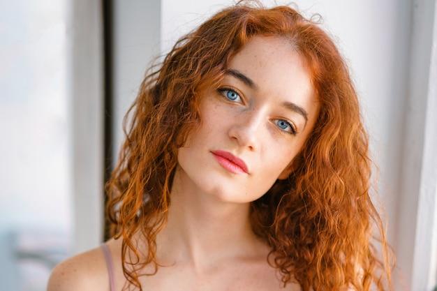 Groot portret van een roodharige jonge vrouw met sproeten