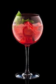 Groot rond wijnglas met verse koude die limonade op zwarte achtergrond wordt geïsoleerd