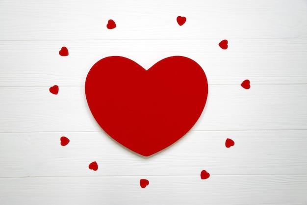 Groot rood hart met vele kleine harten op wit bord. valentijnsdag plat leggen