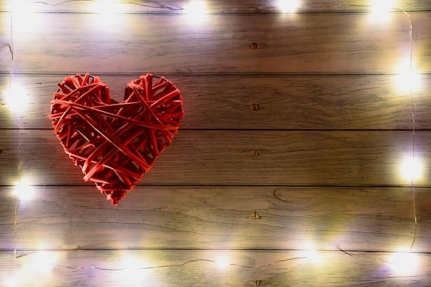 Groot rood rieten decoratief hart aan de linkerkant op een houten ondergrond. er zijn gloeiende lichten rond het frame. aan de rechterkant is er een plaats voor een inscriptie voor verschillende feestdagen.
