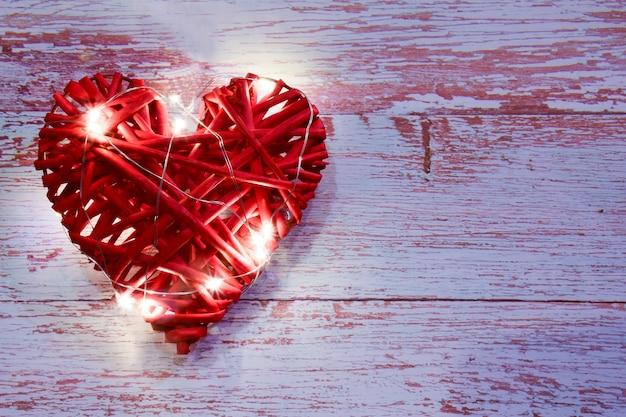 Groot rood rieten decoratief hart aan de linkerkant tegen een achtergrond van houten planken. er zijn gloeiende lichten op. aan de rechterkant is er een plaats voor een inscriptie voor verschillende feestdagen.