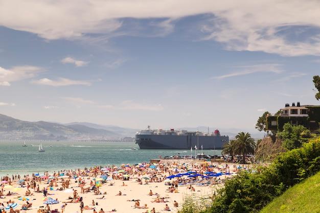 Groot schip in de buurt van dichtbevolkt strand