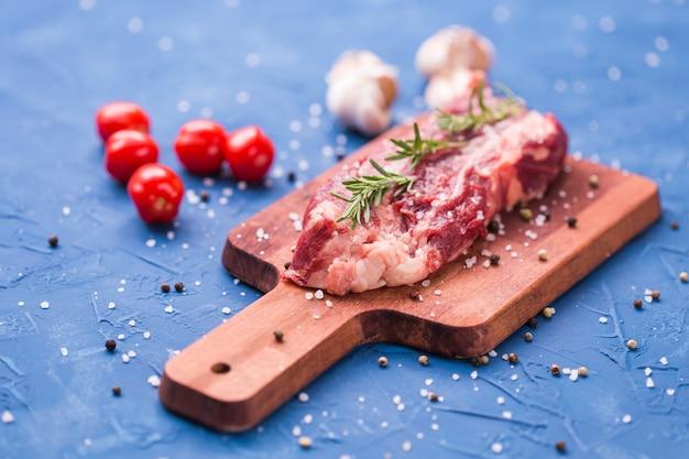 Groot stuk biefstuk op een houten snijplank met rozemarijn en kruiden