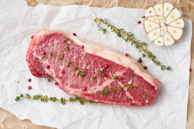Groot stuk rauw rundvlees, lendenen op wit perkamentpapier op papier ambachtelijke