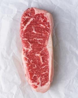 Groot stuk rauw rundvlees, ossenhaas op wit perkamentpapier, verpakking zonder afval.