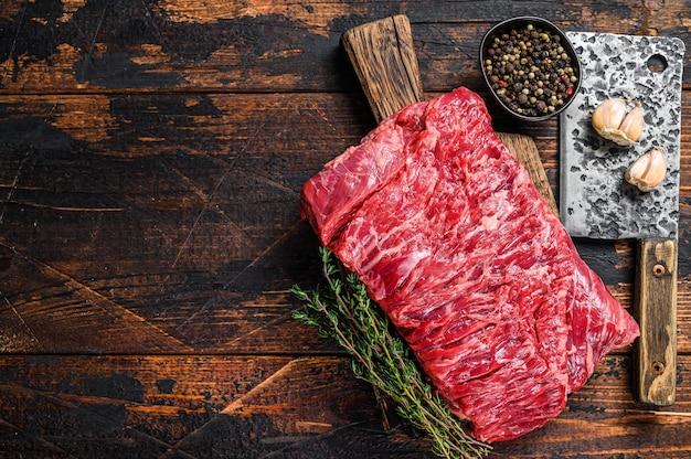 Groot stuk rauwe runderborst gesneden vlees met kruiden en slager hakmes. donkere houten achtergrond. bovenaanzicht. ruimte kopiëren.