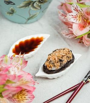 Groot stuk sushi nori met sojasaus in witte bladvorm schotel met bloemen rond.